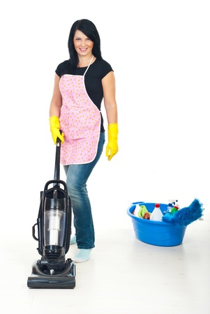 Cute brunette woman with pink apron using vacuum cleaner on floor in her home