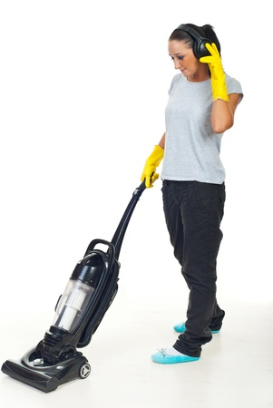 Young woman listening music in headphones and doing housework  photo