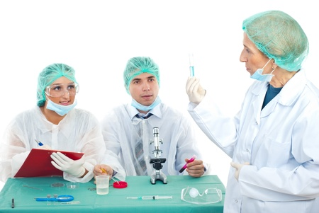 Senior teacher woman showing a tube with blue liquid to her students in laboratory Stock Photo - 8333078