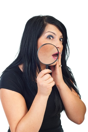 Scared woman with acne holding a magnifying glass and check her face in the mirror isolated on white background