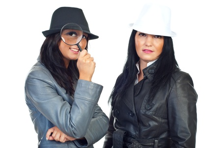 Portrait of two beautiful detectives women with hats holding magnifying glass isolated on white background photo