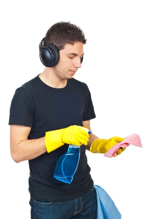 Young man with headphones cleaning house and spraying liquid on duster photo