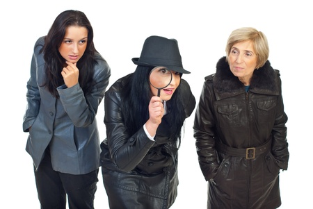Three detectives women at work ,one of them looking through magnifying glass and being surprised photo
