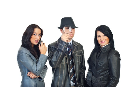 Detective man with magnifying glass in the middle of two beautiful assistants women isolated on white background photo