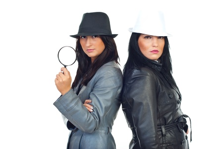 Two beauty young detectives women with hats and leather jackets holding magnifying glass isolated on white background photo
