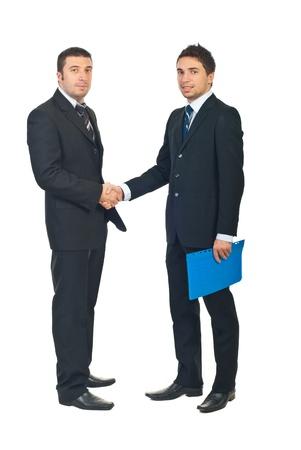dandose la mano: Longitud total de dos hombres de negocios, agitando las manos y uno de ellos mantiene una carpeta con contrato aislado sobre fondo blanco Foto de archivo