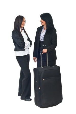 Full length of two beautiful business women with luggage having conversation before trip and smiling together isolated on white background photo