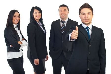 Successful businessman giving thumbs up and his people team smiling in background photo