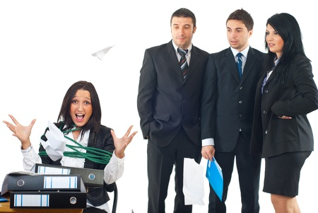 Tied business woman in a chair at desktop being furious and  throwing papers by much work while her colleagues looking with surprised faces  at her photo