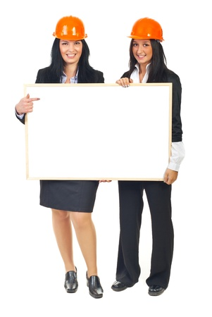 Full length of two architects women holding a blank banner and wearing orange helmets isolated on white background photo