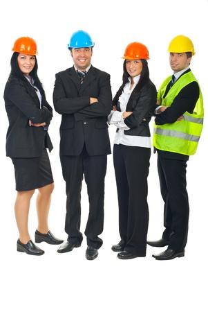 mains crois�es: Toute la longueur des quatre architectes debout dans une ligne avec les mains crois�es et portant des casques color�s isol�s sur fond blanc