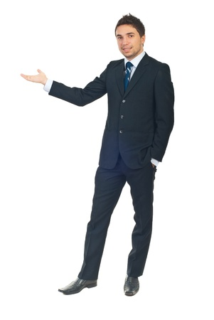 welcoming: Full length of business man in black suit making presentation to copy space isolated on white background Stock Photo