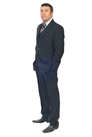 Mid adult business man standing in semi profile with hands in pockets suit isolated on white background photo