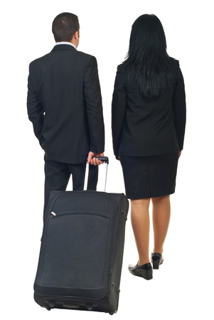 Back of two business people or steward and stewardess going to travel and holding luggage isolated on white background photo