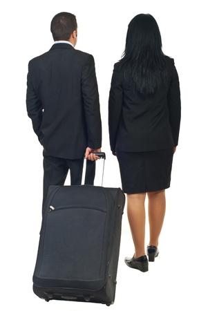 Parte trasera de dos empresarios o mayordomo y azafata va a viajar y equipaje de explotación aislaron sobre fondo blanco