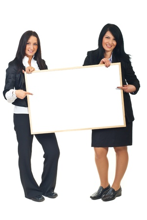 Full length of two business women holding blank placard and pointing to copy space isolated on white background photo