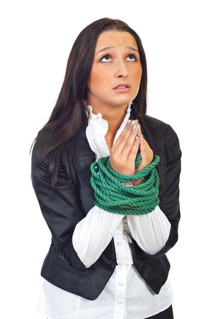 female prisoner: Young executive woman with hands tied praying and looking up isolated on white background