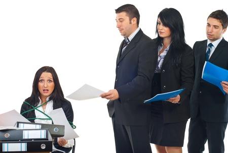 file d attente: Serviteur stress� occup� public li� dans une chaise de bureau travail dur et autres personnes debout dans une ligne et attendent leur tour pour lui donner � ses dossiers de plus de travail