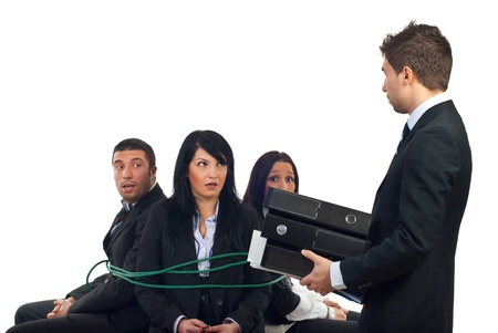 Chief  bring more folders to his shocked employees tied in chiars and force them to work overtime Stock Photo - 8375508
