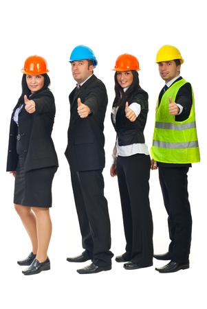 Full length of four engineers with helmet standing in profile and giving thumbs up isolated on white background photo