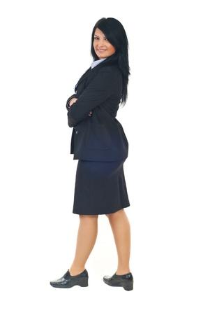 mani incrociate: Lunghezza totale di donna bella business nel profilo in piedi con le mani incrociate e guardando la fotocamera isolata su sfondo bianco