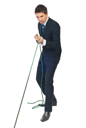 Full length of business man trying hard to pulling rope isolated on white background Stock Photo - 8375526