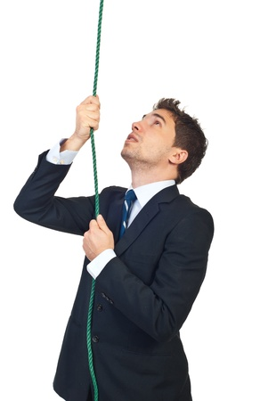 Young business man climbing a rope and looking up isolated on white background Stock Photo - 8375539