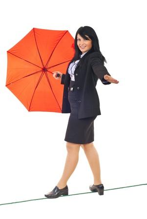 gehhilfe: Beautiful executive Woman walking on a tight Rope und halten Ihr Gleichgewicht mit einem roten Regenschirm isolated on white background