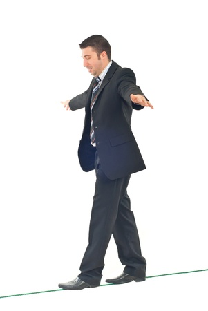 Business man on tightrope  concentrate to  walking isolatedon white background photo