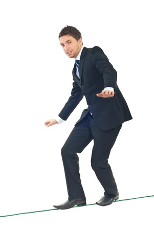 equilibrium: Young businessman walking on tightrope and trying to keep his balance isolated on white background Stock Photo