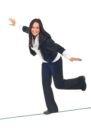 equilibrium: Business woman walking on a tight rope and trying to keep her balance isolated on white background