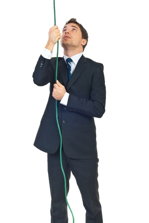 Young business man trying to climbing rope and looking up isolated on white background photo
