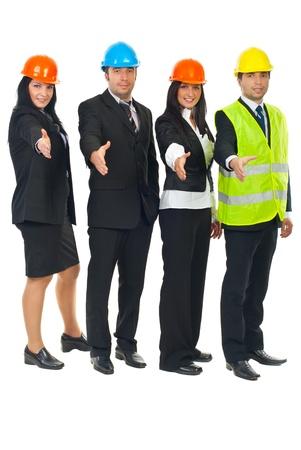 manos estrechadas: Grupo de cuatro arquitectos en una fila con las manos abiertas en el apret�n de manos aislada sobre fondo blanco Foto de archivo