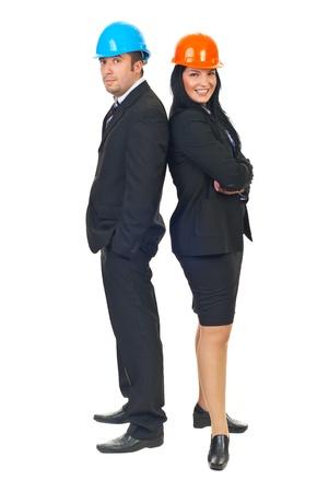 Longitud total de dos ingenieros atractivo hombre y mujer espalda contra espalda de pie y sonriente aislado sobre fondo blanco