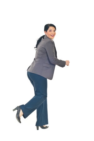 Full length of business woman running  from something and looking back with a surprised happy face isolated on white background photo