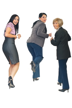 Rear view of three business women running from something or someone  looking back with happy faces isolated on white background photo