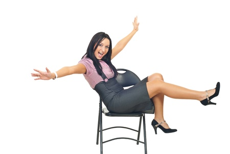 Happy business woman sitting with chair and raising her hands and legs photo