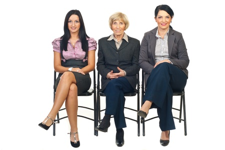 Row of business women sitting on chairs and waiting isolated on white background Stock Photo - 8435977
