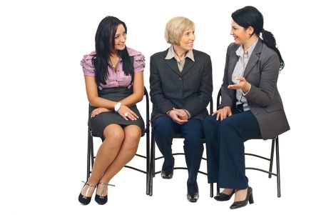 Three business women having conversation at conference and sitting together on cgairs isolated on white background Stock Photo - 8435980