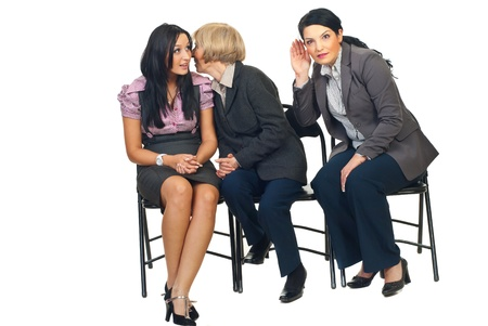 telling: Senior business woman tell a secret  to a colleague woman and other woman trying to hear what her colleagues saying and sitting  all on chairs isolated on white background