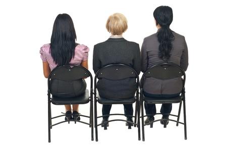 mujeres de espalda: Parte posterior de tres mujeres de negocios sentados en sillas en presentaci�n aislaron sobre fondo blanco