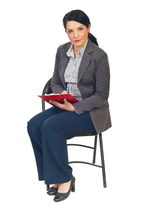 Serious business woman sitting on chair and taking notes isolated on white background photo