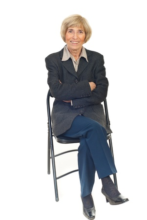 Happy senior business woman sitting on chair isolated on white background