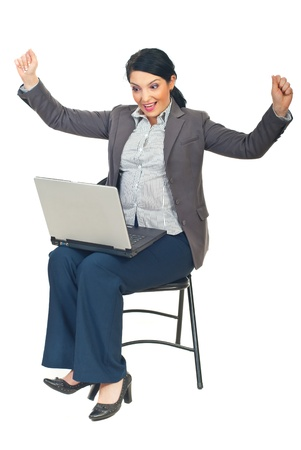 Successful executive woman with laptop sitting on chair and cheering isolated on white background photo