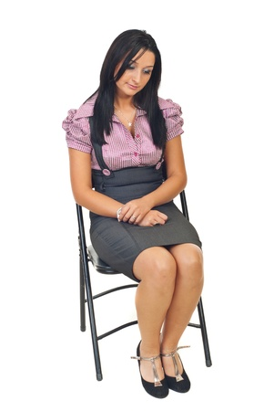 grimace: Sad young corporate woman sitting on chair and looking down isolated on white background