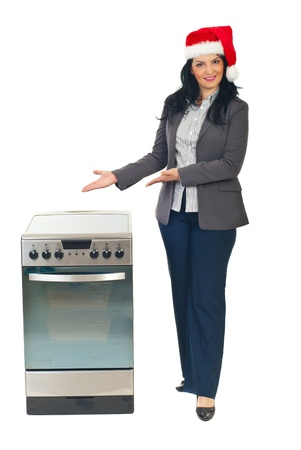 Beautiful woman with santa hat making promotion to a electricical stove and presenting with hands to objects isolated on white background photo