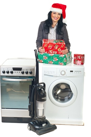 Beautiful saleswoman with Santa hat making pomotion to household appliances and holding Christmas gifts photo