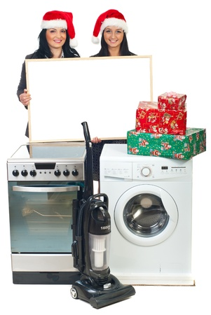 Two beautiful women with Santa hats holding blank banner and making Christmas offer at household appliances photo