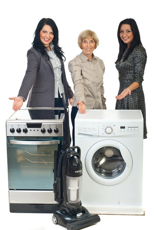 Group of three sales women showing with their hands to household appliances Stock Photo