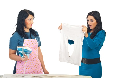 Woman in pink apron burned  her friend shirt and both are shocked and surprised  photo